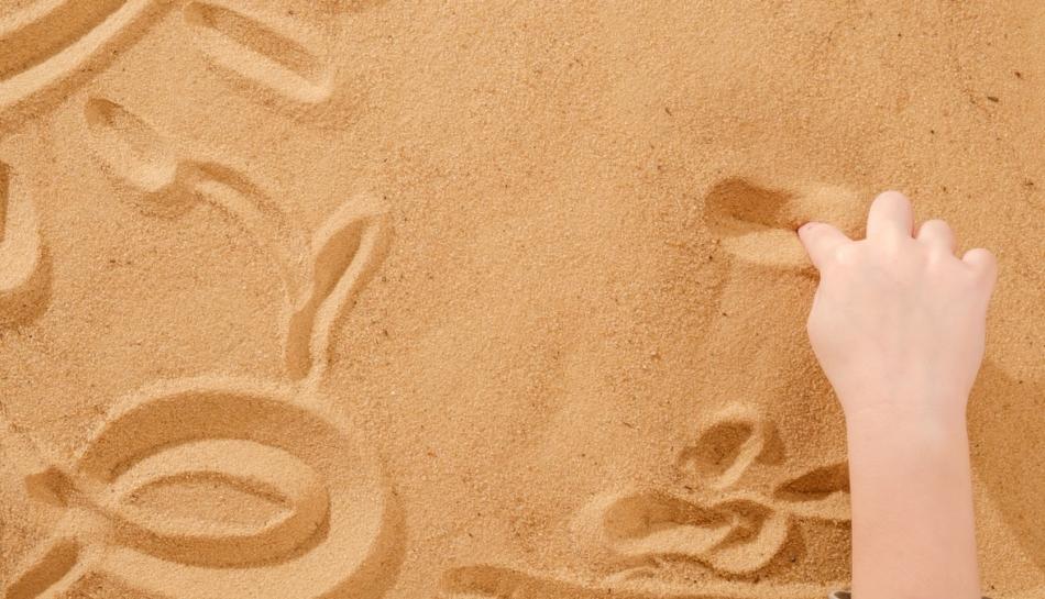 Mano di un bambino che gioca con la sabbia