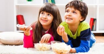 Bambini per terra che mangiano popcorn guardando la tv