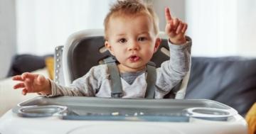 Bambino seduto sul seggiolone fa gesti