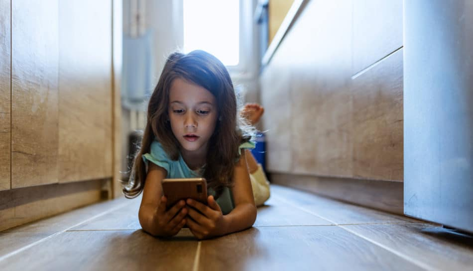 bambina sdraiata per terra che usa uno smartphone