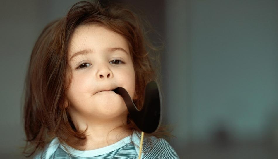 Bambina che finge di fumare con una pipa di carta