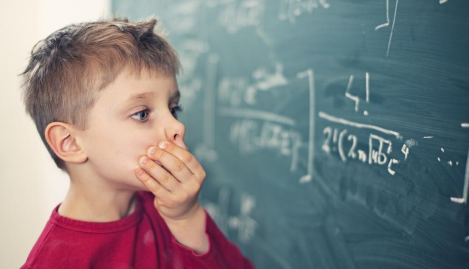 Bambino alla lavagna che risolve un problema di matematica