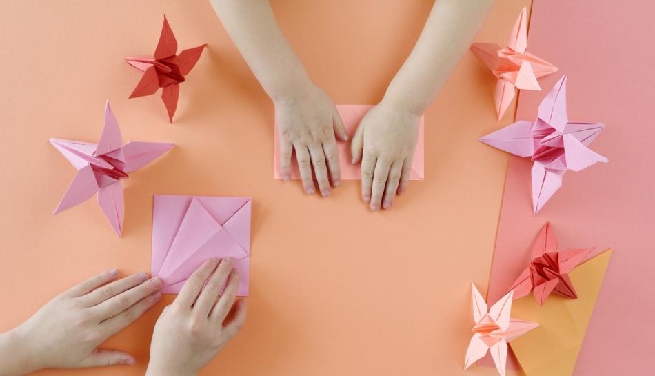 Mani di bambini che realizzano degli origami