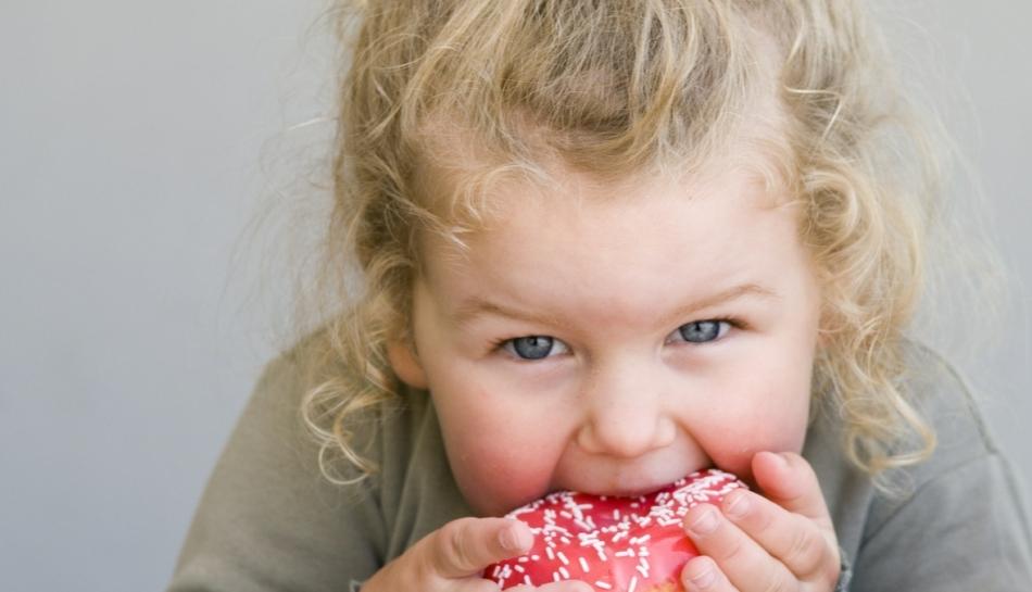 Primo piano di una bambina che addenta una ciambella