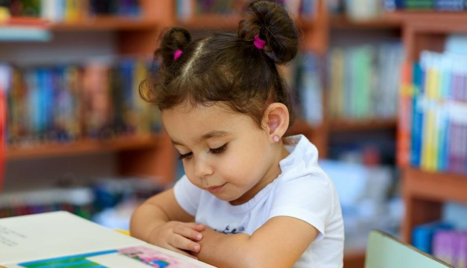 Bambina che legge seduta a un tavolo