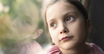 Bambina che guarda triste fuori dalla finestra