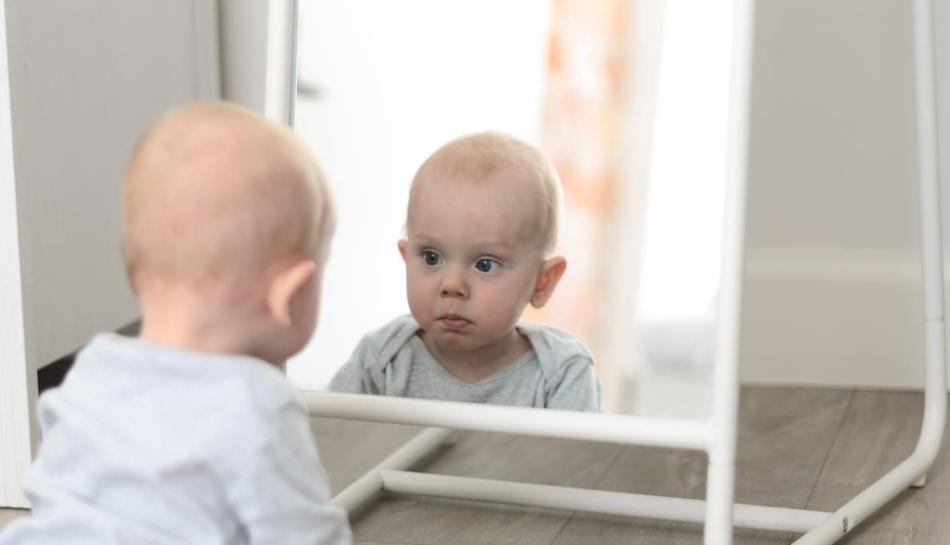 Lattante che si guarda allo specchio