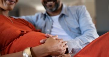 Primo piano delle mani di un papà e una mamma in gravidanza