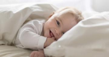Un bambino di circa 7 mesi disteso sul letto e sorridente