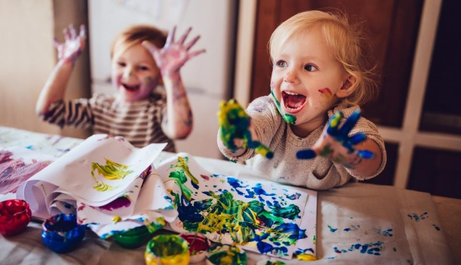 Due bambini seduti al tavolo che giocano con i colori a tempera