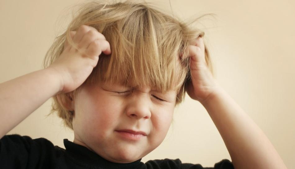 Primo piano di bambino che si tiene la testa tra le mani per il mal di testa