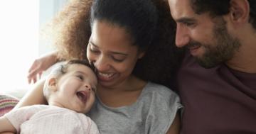 Mamma e papà seduti sul divano abbracciano la loro bambina che ha meno di mille giorni di vita