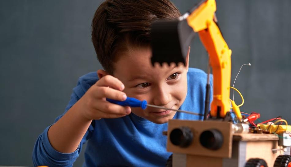 Bambino di circa 6 anni che costruisce un piccolo robot