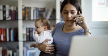 Una mamma tiene in braccio il figlio lattante mentre lavora