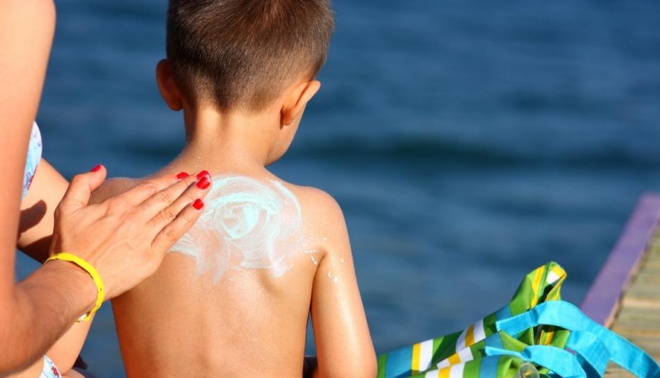 mamma che spalma la crema solare sulla schiena del suo bambino
