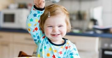 Bambina piccola che agita ridendo il cucchiaio prima di mangiare, in un'atmosfera serena che evita lo sviluppo di disturbi alimentari