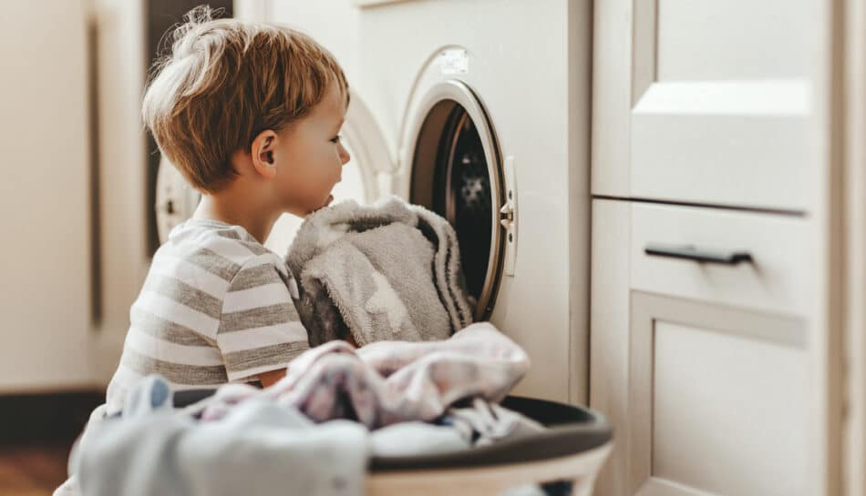 Bambino che si dedica alle faccende domestiche in famiglia, caricando la lavatrice