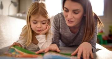 Bambina che legge un libro di fiabe in compagnia di uno dei suoi genitori, la mamma
