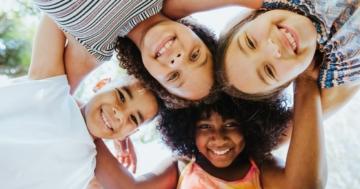 gruppo di bambini di origine diversa abbracciati