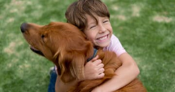 Un bambino abbraccia felice il suo cane
