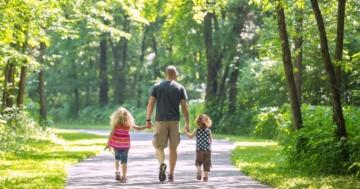 Un papà con i suoi bambini, di schiena, camminano in un ambiente naturale, tutelando la propria salute