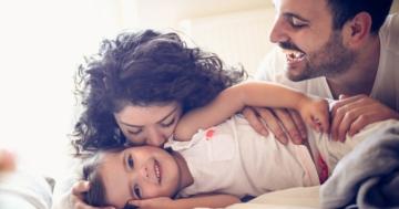 Bambina sdraiata e coccolata dalla mamma e dal papà