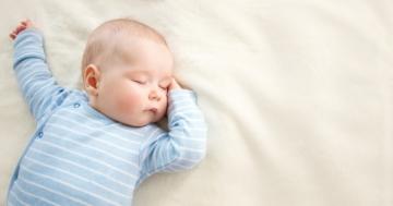 Lattante che dorme a pancia in su, sdraiato su una coperta