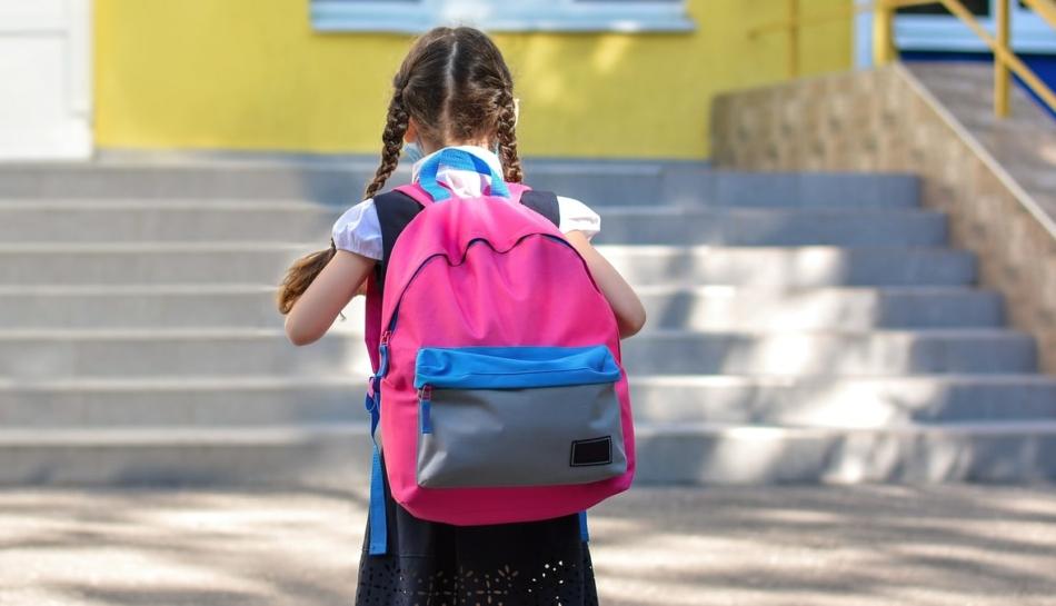 bambina di schiena con zaino sulle spalle che sta per cominciare la prima elementare a settembre