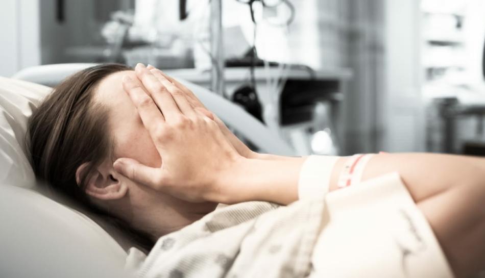 donna in attesa di partorire che si copre il volto con le mani per il timore di incorrere in episodi di violenza ostetrica