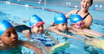Bambini in piscina durante una lezione di nuoto con la loro insegnante