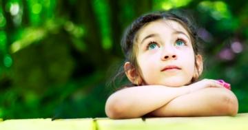 Primo piano di bambina che guarda pensierosa verso l'alto, appoggiata sugli avambracci