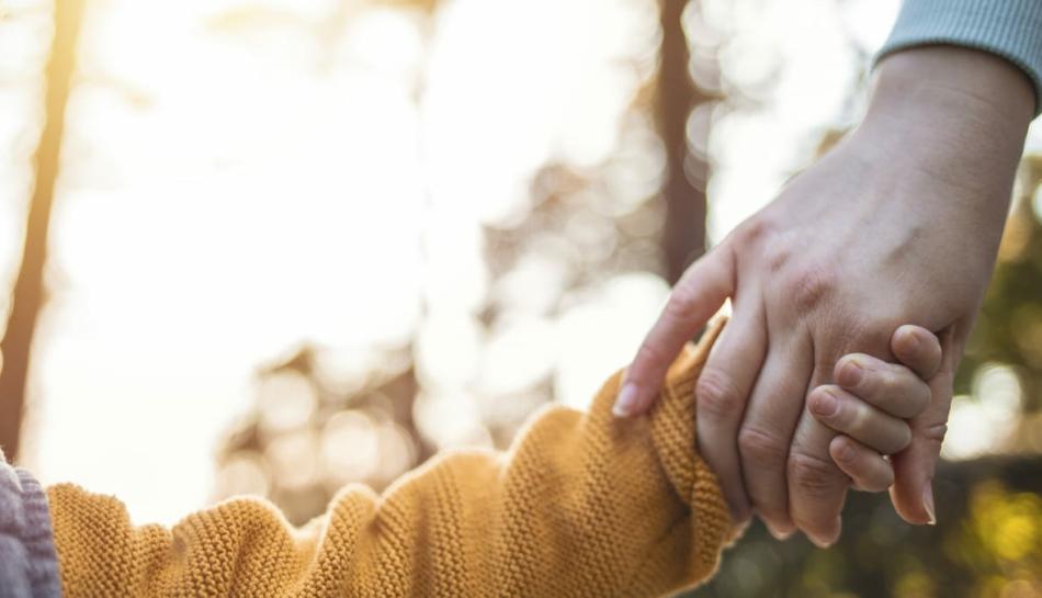 bambino adottato per mano con la mamma
